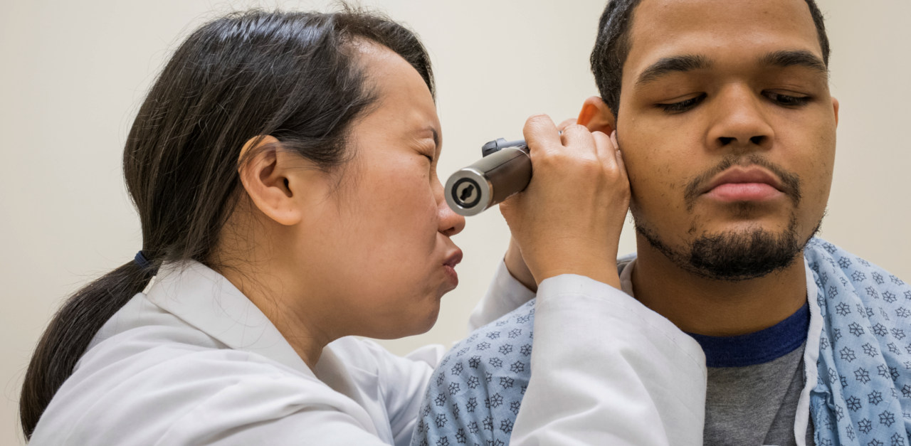 A nurse examines a patient ear with an otoscope