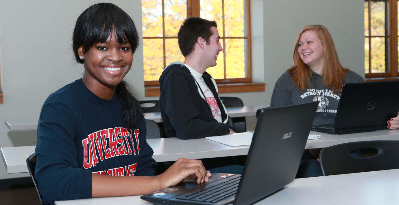 Student with Detroit Mercy sweatshirt in class with laptop.